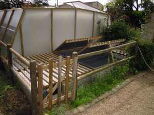 Vue d'ensemble des bassins terminés, avec la clôture de protection et l'adossement à la serre