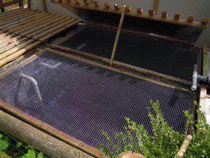 Installation d'un écran grillagé pour parer aux sauts des truites hors bassin, protéger les petits animaux d'une chute dans les bassins, empêcher les prélèvements par le héron et empêcher les feuilles de tomber dans les bassins à l'automne.