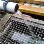 Écoulement de l'eau des bacs vers les fosses à truites via un siphon calibré